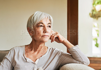 Buy stock photo Cropped shot of an attractive senior woman sitting alone on the sofa and looking contemplative at home