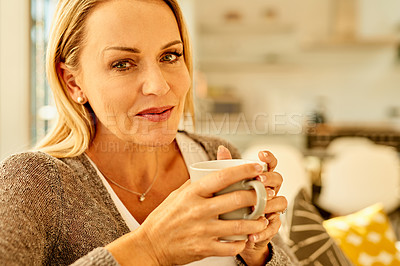 Buy stock photo Shot of an attractive mature woman enjoying a cup of coffee on the sofa at home