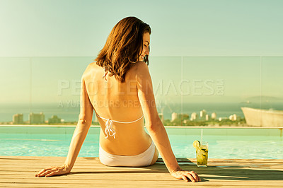 Buy stock photo Shot of a woman having a drink while relaxing by the pool on a sunny day