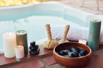 Buy stock photo Cropped shot of hot stones and hot compresses laid out among candles at a spa during the day