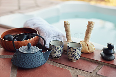 Buy stock photo Cropped shot of a tea set laid out among hot stones and hot compresses at a spa during the day