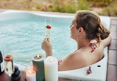 Buy stock photo Cropped shot of an attractive young woman sitting in a jacuzzi and enjoying a glass of champagne at a spa