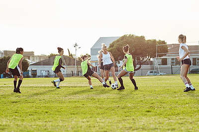 Buy stock photo Full length shot of a group of young women practicing and playing a soccer match together outdoors on the field