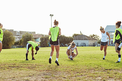 Buy stock photo Full length shot of a group of young sportswomen stretching and warming up together on a sports field