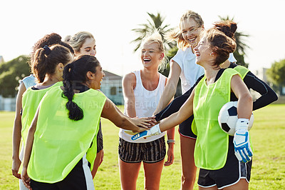 Buy stock photo Cropped shot of a team of young female soccer players joining their hands together for a huddle on the field