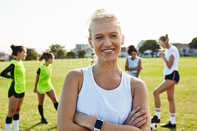 Buy stock photo Portrait of an attractive young female soccer player posing on the field with her teammates in the background