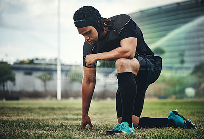 Buy stock photo Full length shot of a handsome young rugby player kneeling down on the field during the day