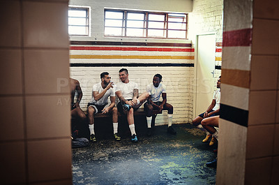 Buy stock photo Full length shot of a group of handsome young rugby players having a chat while sitting together in a locker room