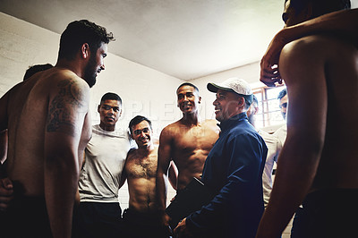 Buy stock photo Cropped shot of a rugby coach addressing his team players in a locker room during the day
