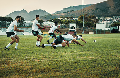 Buy stock photo Full length shot of a group of young rugby players training with bands on the field during the day