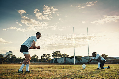 Buy stock photo Full length shot of two young rugby players training together on the field during the day
