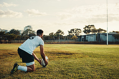 Buy stock photo Full length shot of a handsome young rugby player preparing for a kick while training on the field during the day