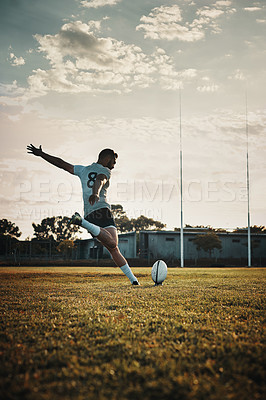 Buy stock photo Full length shot of a handsome young rugby player kicking a ball on the field during the day
