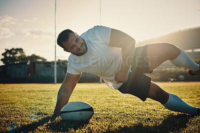 Buy stock photo Cropped shot of a handsome young rugby player training on the field during the day