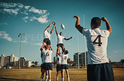 Buy stock photo Cropped shot of two handsome young rugby players catching the ball during a lineout on the field