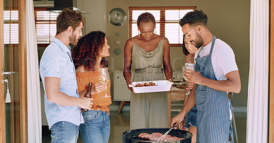Buy stock photo Shot of a group of young friends having a barbecue at home