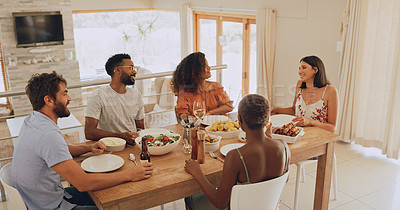 Buy stock photo Shot of a group of young friends getting together for lunch at home
