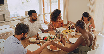 Buy stock photo Shot of a group of young friends praying before sharing a meal together at home