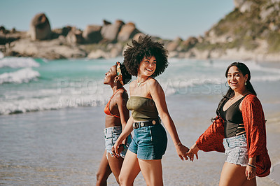 Buy stock photo Shot of three young women enjoying themselves at the beach