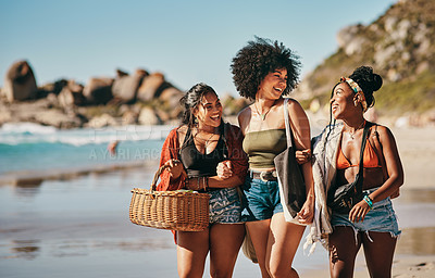 Buy stock photo Shot of three friends arriving at the beach with a picnic basket