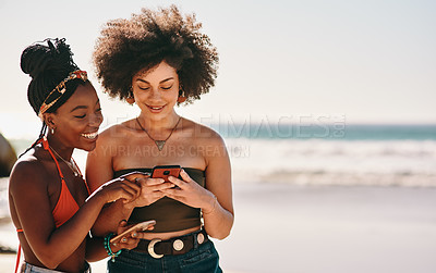 Buy stock photo Cropped shot of two young female friends standing together and using a cellphone at the beach