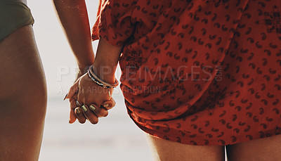 Buy stock photo Cropped shot of two unrecognizable friends standing together and holding hands while on the beach