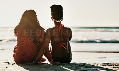 Buy stock photo Full length shot of two unrecognizable friends sitting together during a day out on the beach