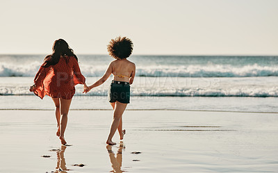 Buy stock photo Full length shot of two unrecognizable friends standing together and holding hands while walking on the beach