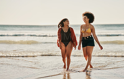 Buy stock photo Full length shot of two attractive female friends bonding together during an enjoyable day on the beach