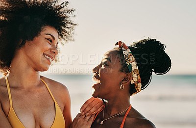 Buy stock photo Cropped shot of two attractive female friends bonding together during an enjoyable day on the beach