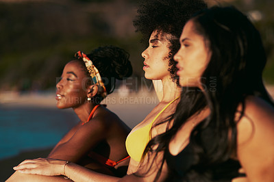 Buy stock photo Cropped shot of three female friends sitting together on the beach