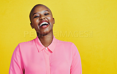 Buy stock photo Portrait of an attractive and cheerful young woman posing in studio against a yellow background