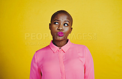 Buy stock photo Cropped shot of an attractive young woman looking curious and thoughtful against a yellow background