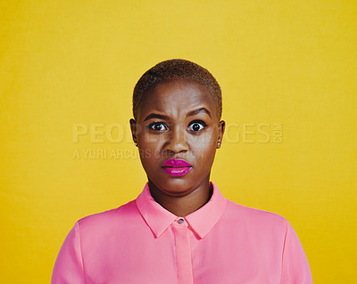 Buy stock photo Portrait of an attractive young woman looking stunned in studio against a yellow background