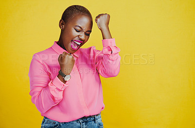 Buy stock photo Cropped shot of an attractive young woman celebrating and feeling cheerful against a yellow background