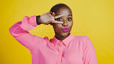 Buy stock photo Portrait of an attractive young woman posing and making the peace hand gesture in studio against a yellow background