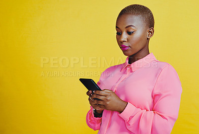 Buy stock photo Cropped shot of an attractive young woman using her cellphone in studio against a yellow background