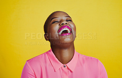 Buy stock photo Cropped shot of an attractive and cheerful young woman posing in studio against a yellow background