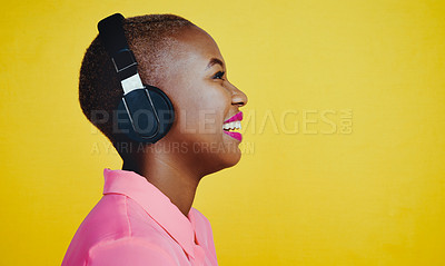 Buy stock photo Cropped shot of an attractive young woman listening to music on headphones against a yellow background