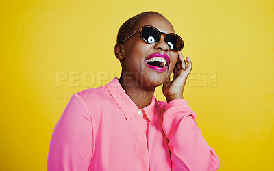 Buy stock photo Cropped shot of an attractive young woman wearing sunglasses posing in studio against a yellow background