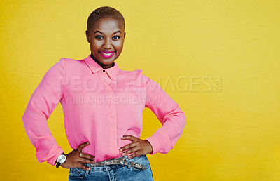 Buy stock photo Portrait of an attractive and confident young woman posing in studio against a yellow background