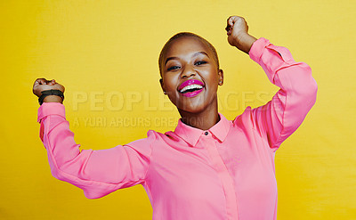 Buy stock photo Portrait of an attractive and cheerful young woman dancing in studio against a yellow background