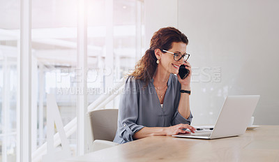 Buy stock photo Shot of a mature businesswoman talking on a cellphone while working on a laptop in an office