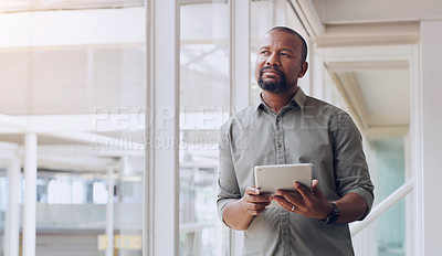 Buy stock photo Shot of a mature businessman looking thoughtful while using a digital tablet in an office