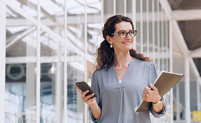 Buy stock photo Shot of a mature businesswoman using a cellphone while walking in an office