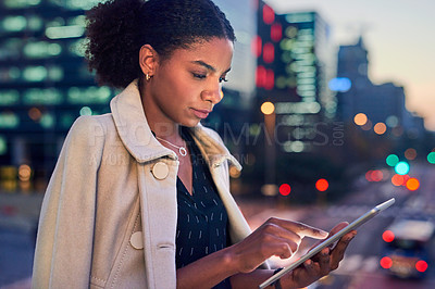 Buy stock photo Cropped shot of an attractive young businesswoman using a digital tablet outdoors in the evening with the cityscape in the background