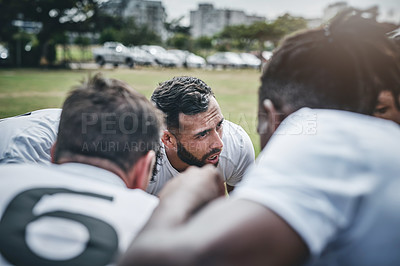 Buy stock photo Cropped shot of a focused young rugby team forming a huddle before a match outside on a rugby field