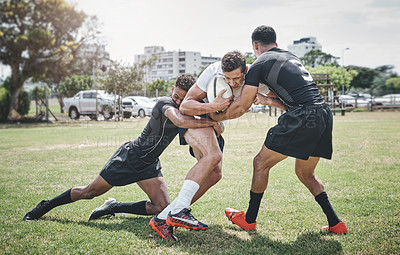 Buy stock photo Shot of a focused young rugby player competing against his opponents during a match outside on a filed