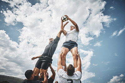 Buy stock photo Low angle shot of two rugby teams competing over a ball during a line out of a rugby match outside on a filed