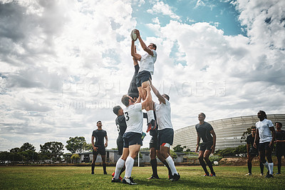 Buy stock photo Shot of two rugby teams competing over a ball during a line out of a rugby match outside on a filed